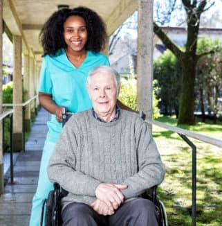 senior man on wheelchair accompanied by his caregiver