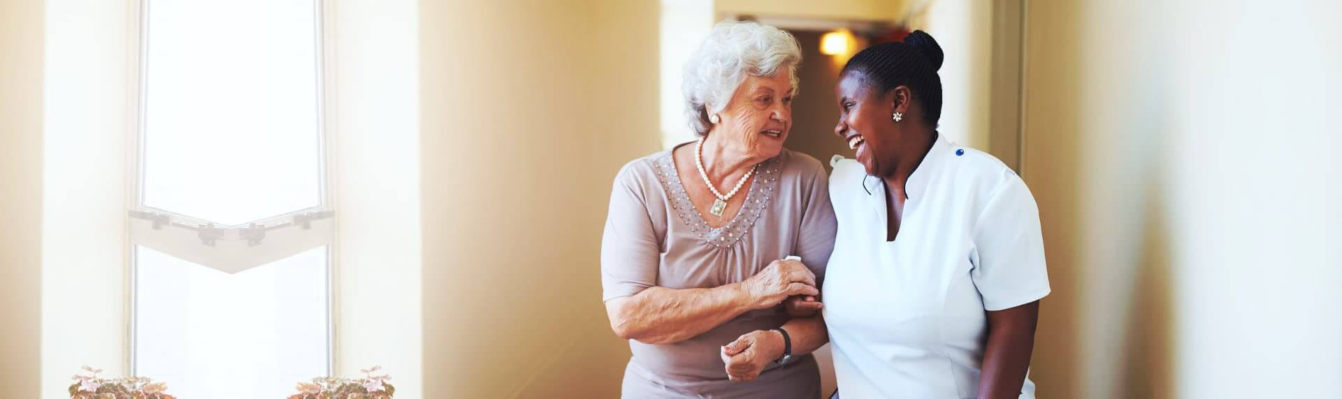 caregiver and senior woman walking together